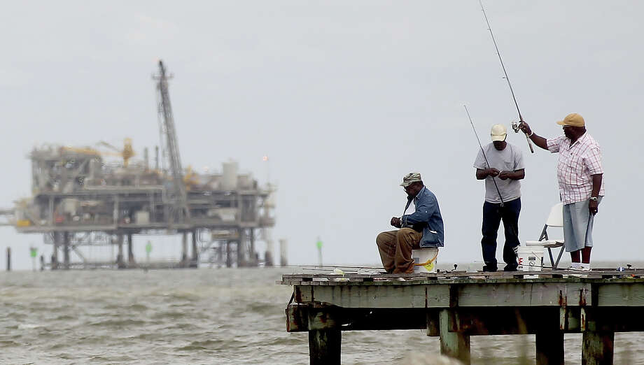 DAUPHIN ISLAND, AL - APRIL 18:  People fish with an oil rig in the background April 18, 2011 in Dauphin Island, Alabama. Dauphin Island's beaches were impacted by oil from the BP oil spill. April 20th marks the one-year anniversary of the worst environmental disaster in U.S. history. Photo: Mario Tama / 2011 Getty Images