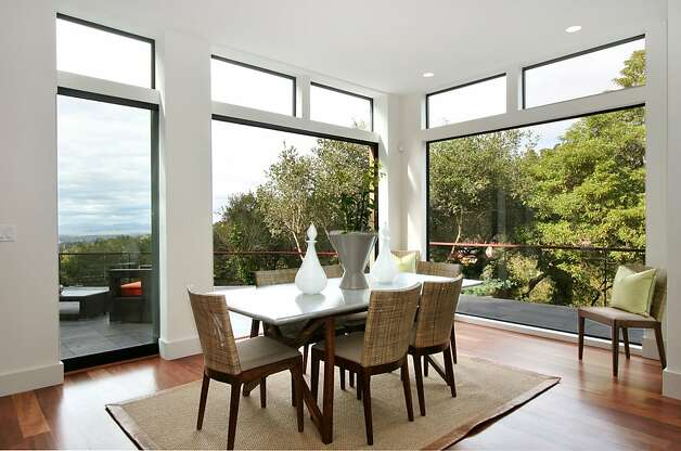 There are more floor-to-ceiling windows in the dining area as well as doors that leads to the deck. Photo: Liz Rusby