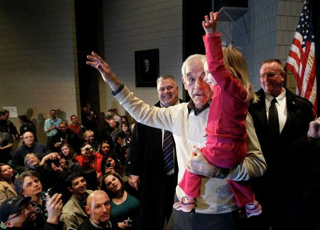 Republican presidential candidate Ron Paul shows 2-year-old Piper DeYoung how to wave to the crowd during a campaign stop Saturday, Feb. 4, 2012, in Rochester, Minn. Photo: Charles Rex Arbogast, Associated Press / AP
