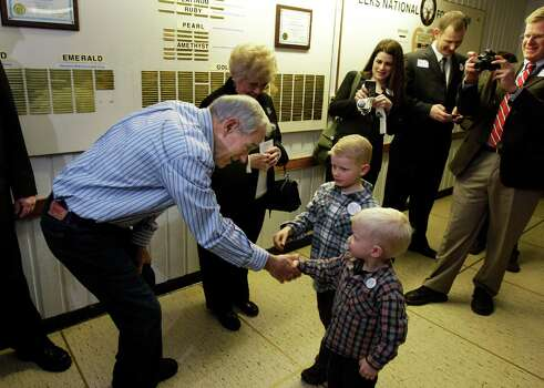 Ron Paul shakes hands with Henry Nichols, 3, and Davis Nichols, 6, as Paul and his wife, Carol, greet people at Washington state caucus meetings, Saturday, March, 3, 2012, in Puyallup, Wash. Photo: Ted S. Warren, Associated Press / AP