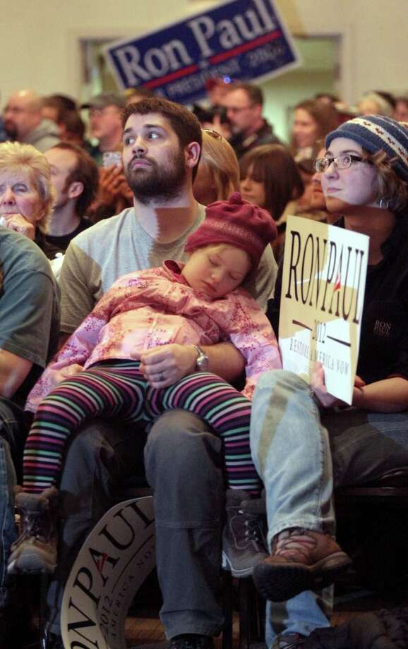 Justin Harvey and his wife, Tanis, listen to Republican presidential candidate Ron Paul as their niece Charity, 5, naps during a rally Sunday, March 4, 2012, in Fairbanks, Alaska. Photo: SAM HARREL, Associated Press / ap