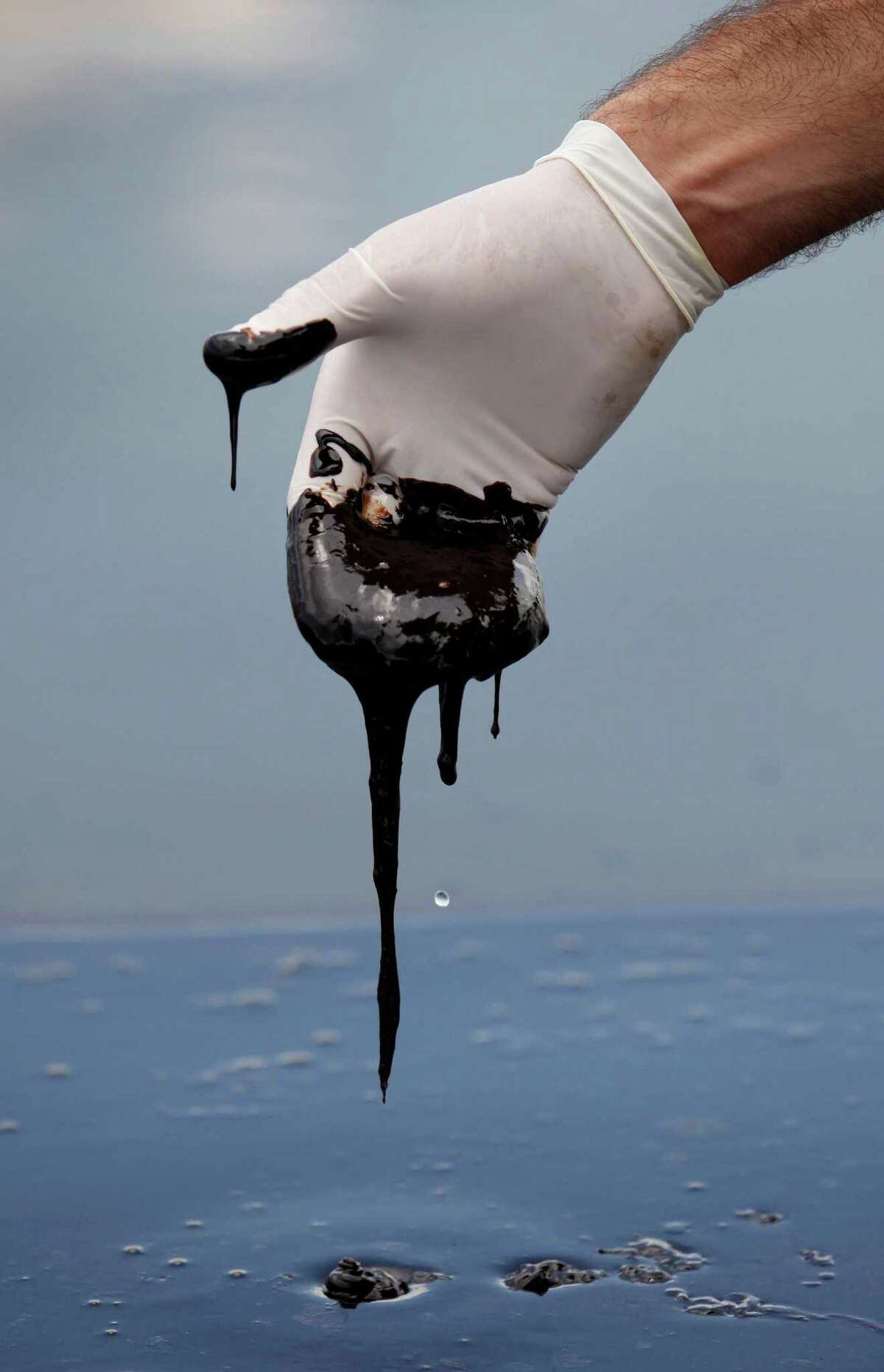 FILE - In this June 15, 2010 file photo, a member of Louisiana Gov. Bobby Jindal's staff wearing a glove reaches into thick oil on the surface of the northern regions of Barataria Bay in Plaquemines Parish, La. An April 20, 2010 explosion at the BP Deepwater Horizon offshore platform killed 11 men, and the subsequent leak released an estimated 172 million gallons of petroleum into the Gulf of Mexico.