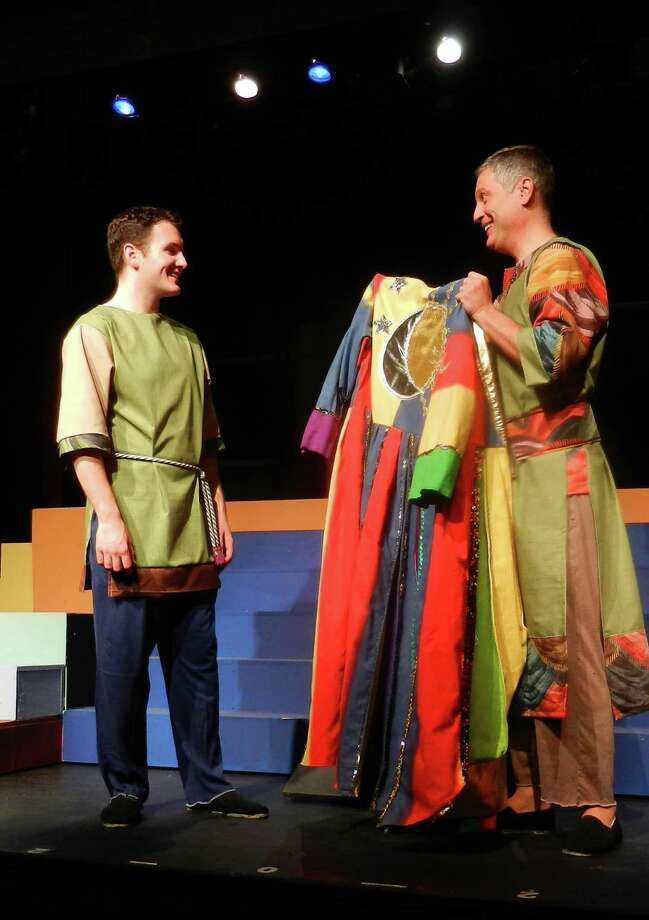 In a true example of art imitating life, George Alberts, (right) who played Joseph at Curtain Call in 2000,  passes down the Amazing Technicolor Dreamcoat to Michael Okulski, the actor playing Joseph in the current production. In the musical, Alberts plays Joseph's father - the one who gives Joseph the coat. Photo: Contributed Photo
