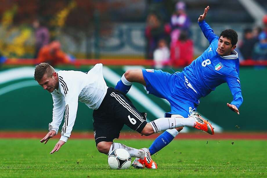 Right in the ol' Keisterbach: Italy's Luca Crecco (right) misses the ball, but he does manage to give Tim Hoelscher of Germany a kick in the pants during a U18 international friendly match in Kelsterbach, Germany. Photo: Alex Grimm, Bongarts/Getty Images