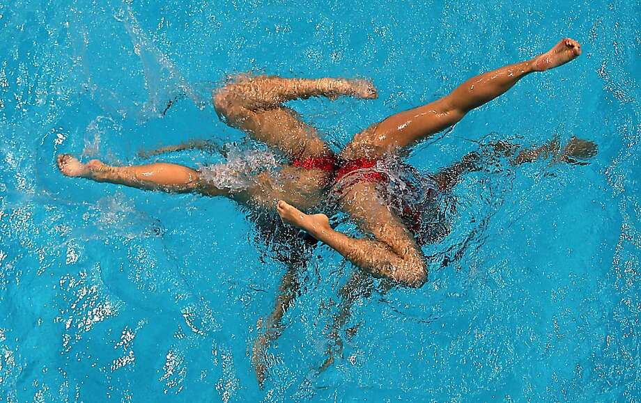 Double dipping: Chinese synchronized swimmers hold their breaths and kick out their toes while performing a challenging routine at the Asian Swimming Championships in Dubai. The pair won the gold in the duet competition. Photo: Karim Sahib, AFP/Getty Images