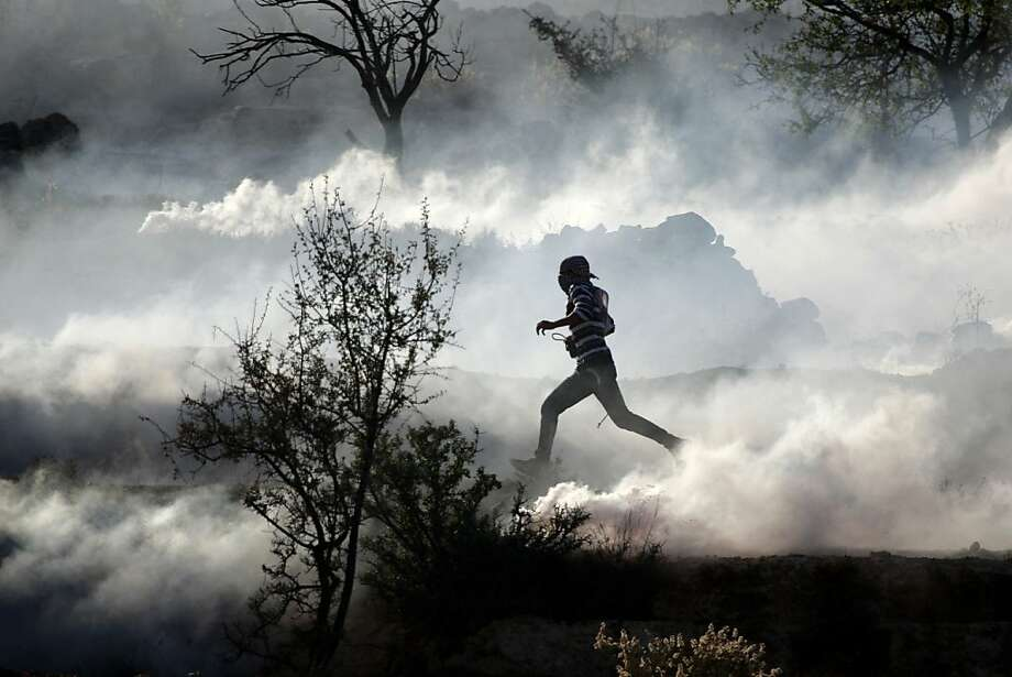 A gantlet of fumes: A Palestinian demonstrator sprints through clouds of tear gas during clashes with Israeli security forces near Ofer, an Israeli military prison near the West Bank city of Ramallah. The Palestinians were protesting Israeli operations in Gaza Strip. Photo: Majdi Mohammed, Associated Press