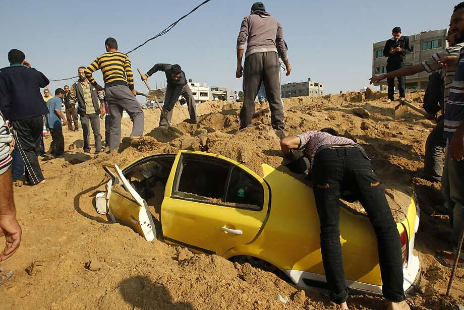 Bloody tit-for-tat: Palestinians try to pull civilians out of a car buried in dirt by an Israeli air strike at Twaam in Beit Lahia, Gaza. Israel has ramped up air attacks in retaliation for rockets fired at Israeli targets. Photo: Mohammed Abed, AFP/Getty Images