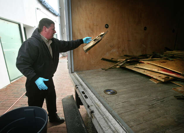 Bill Boughton of Wallingford throws flooding damaged wood flooring from Chico's into the back of a truck outside the store on Main Street in downtown Westport on Thursday, November 15, 2012. Photo: Brian A. Pounds / Connecticut Post