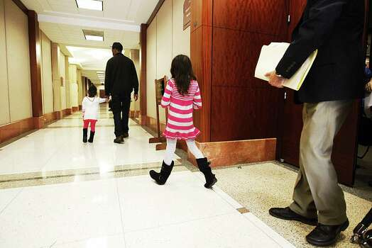 The girl in the striped outfit, one of two witnesses who were children, leaves the project court #1 after testifying in the punishment phase of the Tata trial Thursday, Nov. 15, 2012. Photo: Nick De La Torre, .