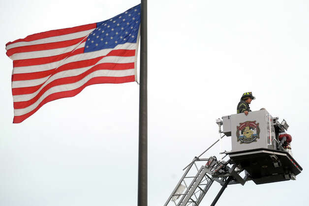 Bridgeport firefighter Arnaldo Torres goes aloft above fire headquarters on the ladder of Tower Ladder 5, the Bridgeport Fire Department's new truck, which was unveiled in Bridgeport, Conn. Nov. 15th, 2012. Photo: Ned Gerard / Connecticut Post