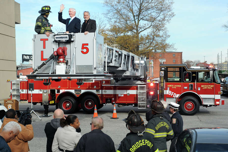 Mayor Bill Finch waves from the ladder bucket on Tower Ladder 5, the Bridgeport Fire Department's new fire truck, which was unveiled at fire headquarters, in Bridgeport, Conn. Nov. 15th, 2012. The mayor was taken aloft with firefighter Arnaldo Torres, left, and fire commissioner Stuart Rosenberg. Photo: Ned Gerard / Connecticut Post