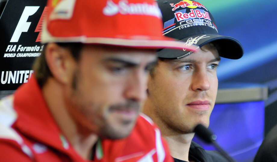 Red Bull driver Sebastian Vettel (right) listens to a question during a Thursday press conference ahead of the United States Grand Prix at Austin's Circuit of the America's. At left is his championship rival, Ferrari's Fernando Alonso. Photo: Robin Jerstad/For The Express-Ne