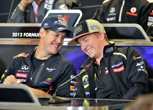 Red Bull driver Sebastian Vettel (left) shares a laugh with Lotus driver Kimi Raikkonen during a Thursday press conference ahead of the United States Grand Prix at Austin's Circuit of the America's. Photo: Robin Jerstad/For The Express-Ne