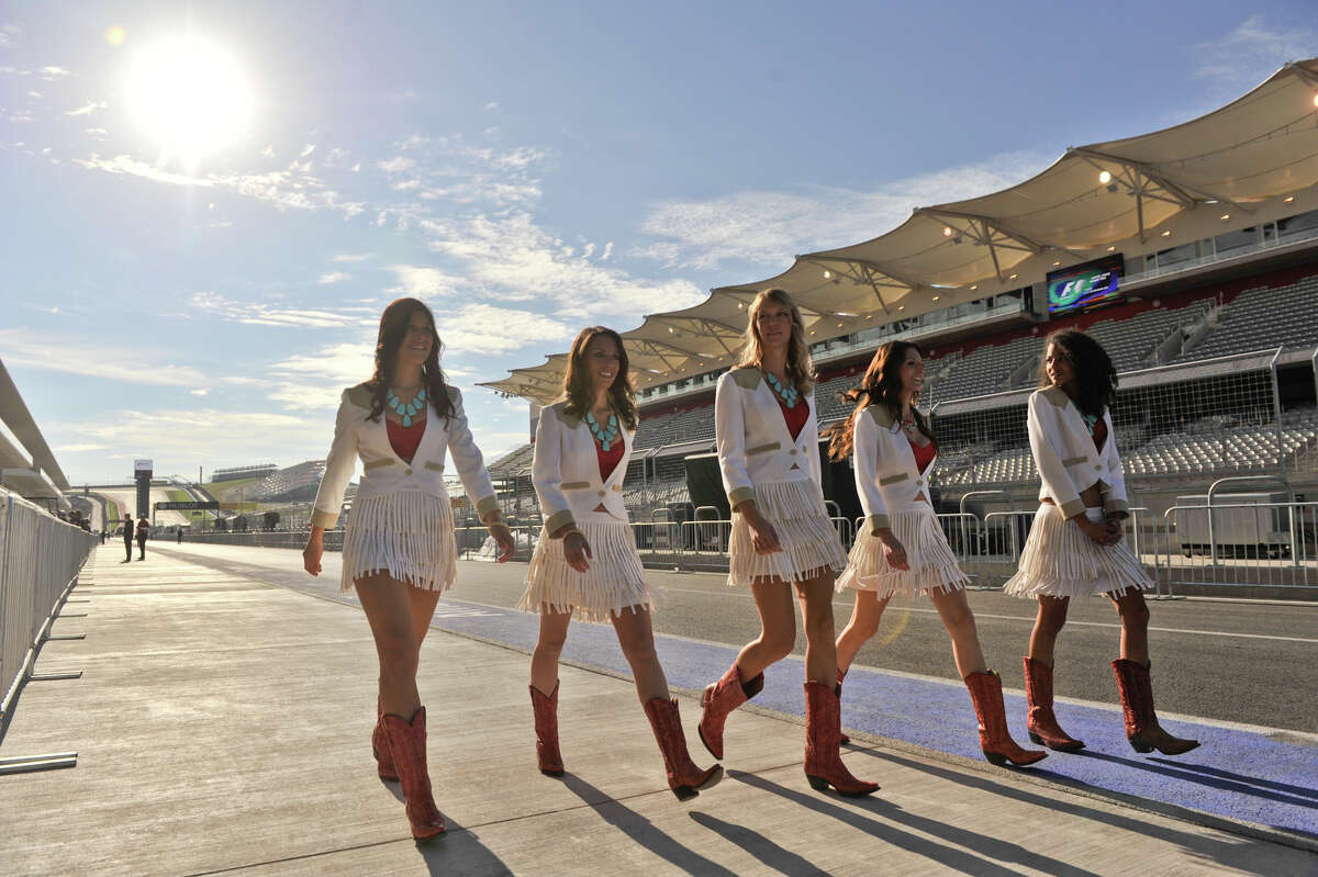 Formula 1 Grid Girls dressed in a Texas motif stroll the pit lane of the Circuit of the America's Thursday morning near Austin.
