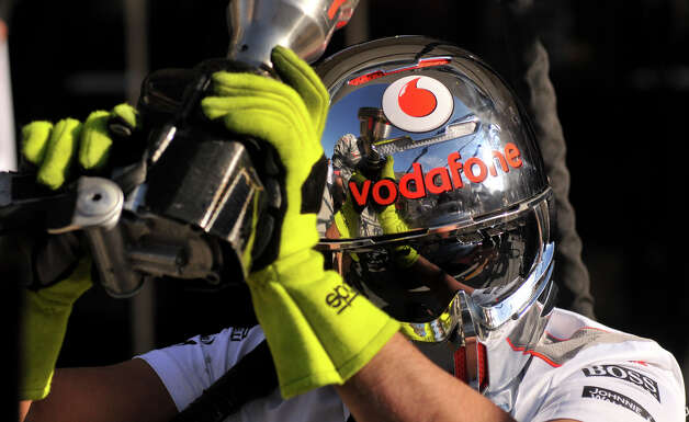 A McLaren crew member wears a protective helmet as the team practices pit stops early Thursday morning at the Circuit of the America's near Austin. Photo: Robin Jerstad/For The Express-Ne