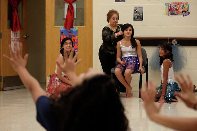 Volunteer Rachel Ponce measures Daisy Beltran, 12, for a hat, center, while Emily Ajuech, 13, left, and Anjelisa Camacho, 12, right, watch their classmates practice their routine in their dance class as they prepare for an upcoming performance of The Nutcracker at the Young Women's Leadership Academy in San Antonio on Wednesday, Nov. 14, 2012. Photo: Lisa Krantz, San Antonio Express-News / © 2012 San Antonio Express-News