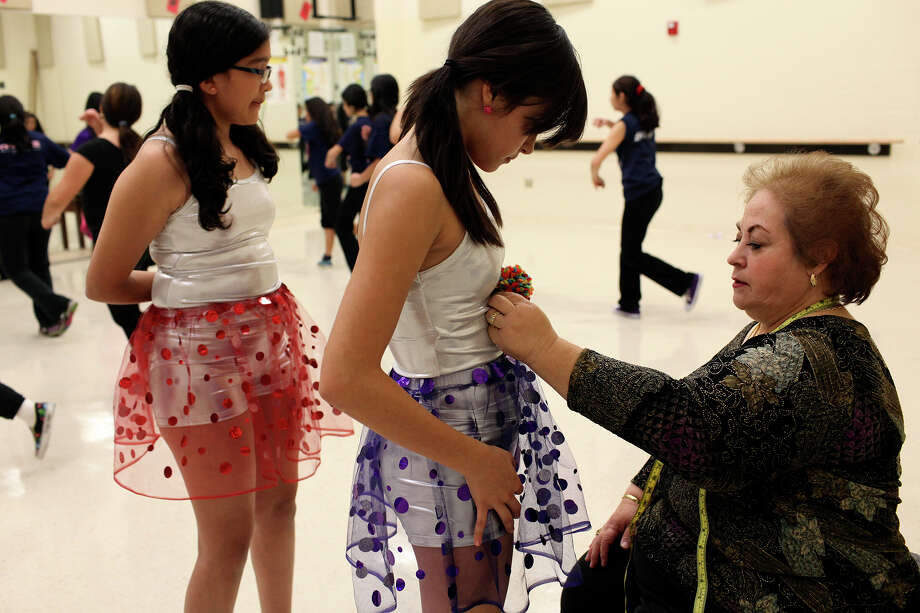 Volunteer Rachel Ponce assesses costume needs for Daisy Beltran, 12, center, and Emily Ajuech, 13, left, so she can create their costumes for their upcoming performance of The Nutcracker at the Young Women's Leadership Academy in San Antonio on Wednesday, Nov. 14, 2012. Photo: Lisa Krantz, San Antonio Express-News / © 2012 San Antonio Express-News