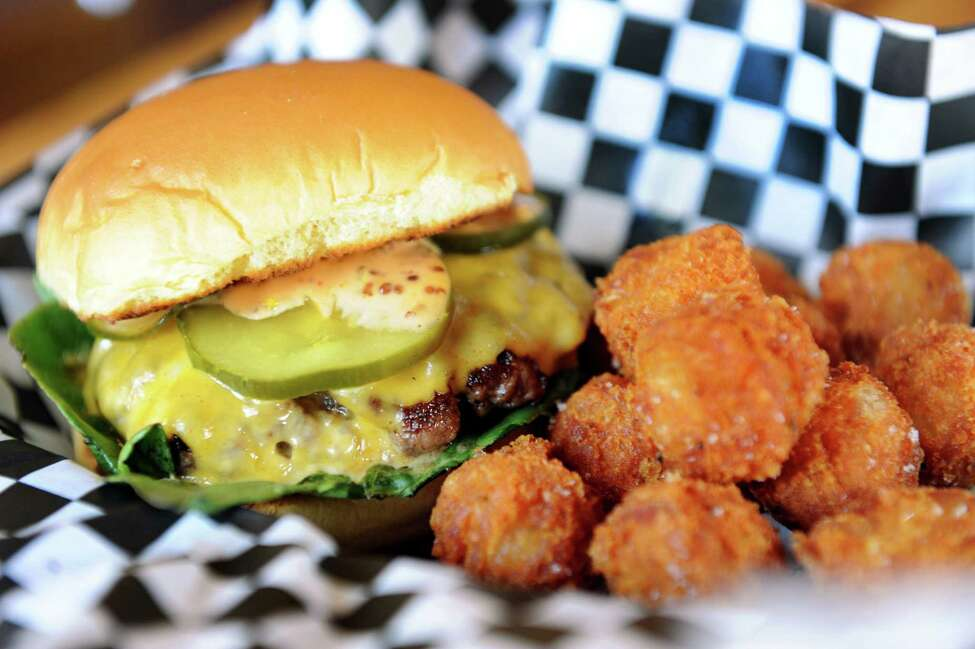 The Comfort Burger with custom-blended beef, American cheese, lettuce and house-made pickles topped with Awesome Sauce on Saturday, Nov. 10, 2012, at the Comfort Kitchen in Saratoga Springs, N.Y. Served with a side of tater tots. (Cindy Schultz / Times Union)