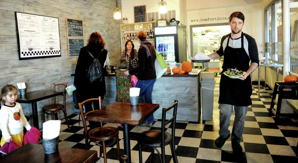Chef Rory Moran, right, delivers lunch to his guests as others place their orders at the counter on Saturday, Nov. 10, 2012, at the Comfort Kitchen in Saratoga Springs, N.Y. (Cindy Schultz / Times Union)