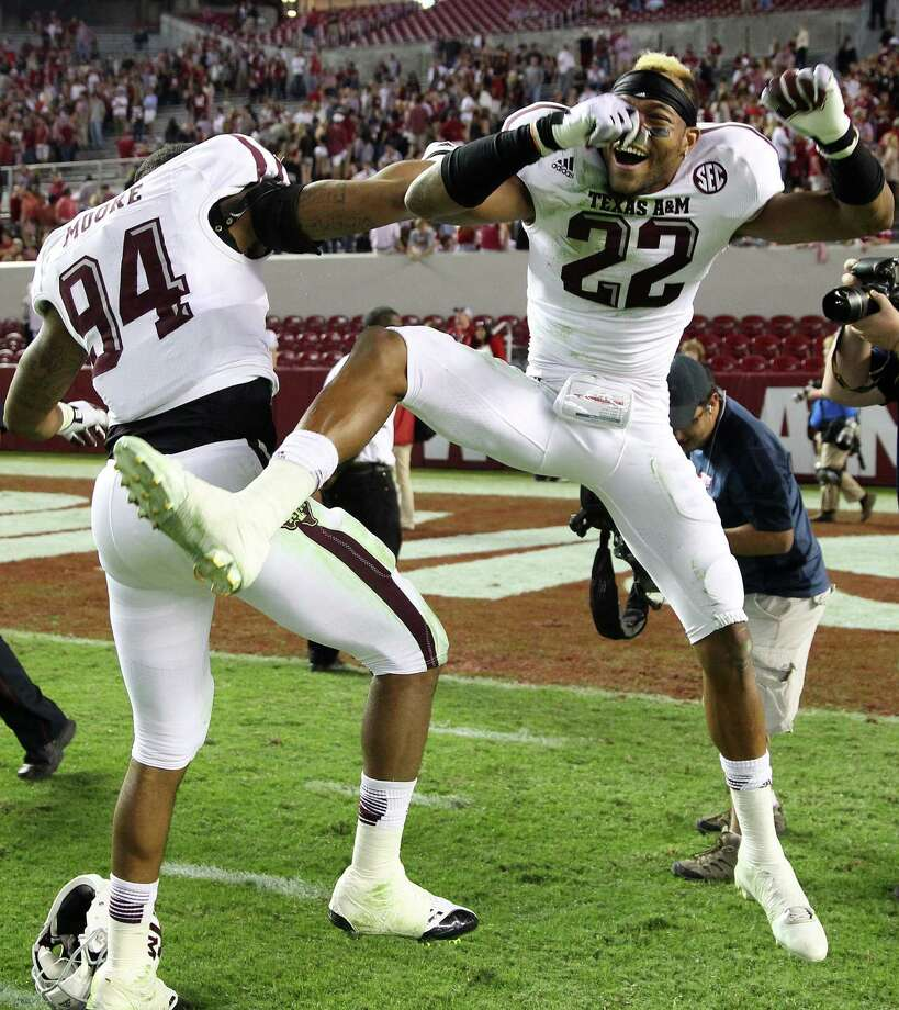 Defensive back Dustin Harris #22 of the Texas A&M Aggies (right) celebrates with defensive lineman and teammate Demontre Moore #94 after the game against the Texas A&M Aggies at Bryant-Denny Stadium on November 10, 2012 in Tuscaloosa, Alabama. Photo: Mike Zarrilli, Getty Images / 2012 Getty Images