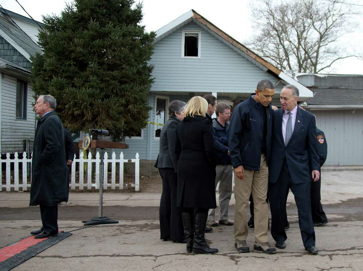 President Barack Obama walks with Sen. Charles Schumer, D-N.Y., from a new conference on Cedar Grove Avenue, a street significantly impacted by Superstorm Sandy, on the Staten Island borough of New York, Thursday, Nov. 15, 2012. At left is New York City Mayor Michael Bloomberg.