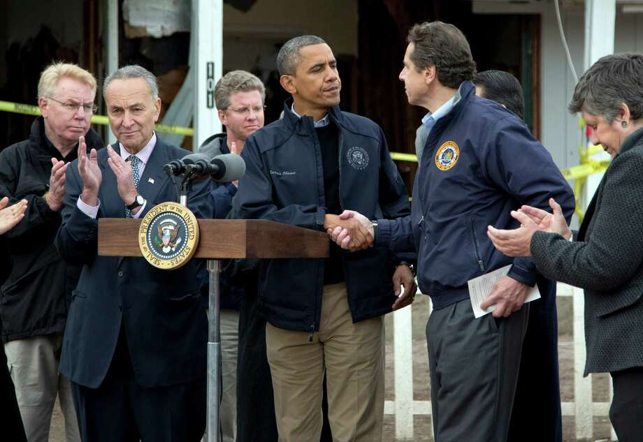 President Barack Obama shakes hands with New York Gov. Andrew Cuomo, during a news conference on  Cedar Grove Avenue, a street significantly impacted by Superstorm Sandy, on Staten Island, Thursday, Nov. 15, 2012, in New York. Sen. Charles Schumer, D-N.Y., is second from left, Secretary of Housing and Urban Development Shaun Donovan is third from left, and Secretary of Homeland Security Janet Napolitano is right. Photo: Carolyn Kaster, AP / AP