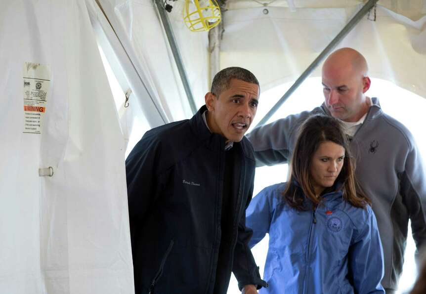 President Barack Obama ducks into a tent  to greet people at a FEMA recovery center on the grounds o