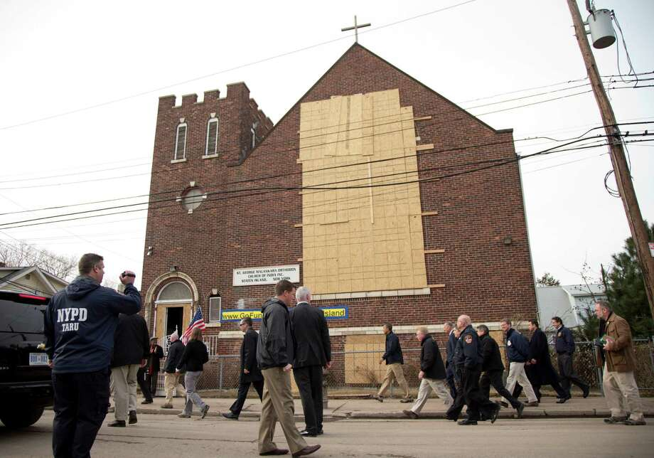 President Barack Obama walks past the St. George Malankara Orthodox Church of India as he tours and visits with people on Cedar Grove Avenue, a street significantly impacted by Superstorm Sandy, on the Staten Island borough of New York, Thursday, Nov. 15, 2012. Photo: Carolyn Kaster, AP / AP