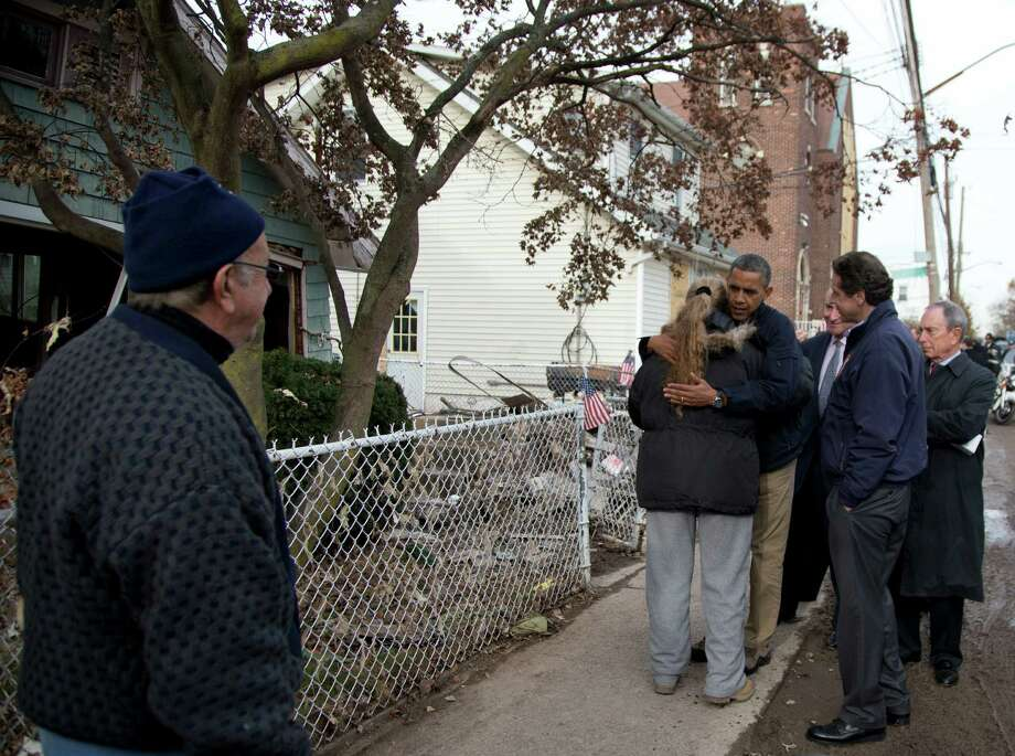 President Barack Obama, accompanied by New York City Mayor Michael Bloomberg, New York Gov. Andrew Cuomo and Sen. Charles Schumer, D-N.Y., hugs Debbie Ingenito on Cedar Grove Avenue, a street significantly impacted by Superstorm Sandy, Thursday, Nov. 15, 2012, on Staten Island, in New York. Photo: Carolyn Kaster, AP / AP