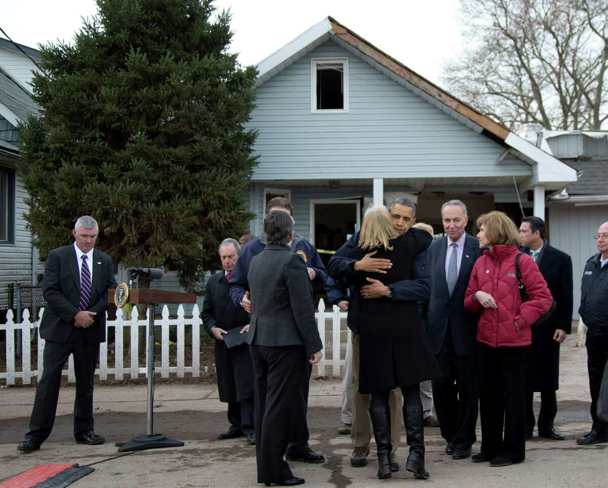 President Barack Obama, accompanied by New York City Mayor Michael Bloomberg, New York Gov. Andrew Cuomo, Homeland Security Secretary Janet Napolitano, Sen. Charles Schumer, D.N.Y., and other, hugs Sen. Kirsten Gillibrand, D-N.Y., after a news conference on Cedar Grove Avenue, a street significantly impacted by Superstorm Sandy, Thursday, Nov. 15, 2012, on Staten Island, in New York.