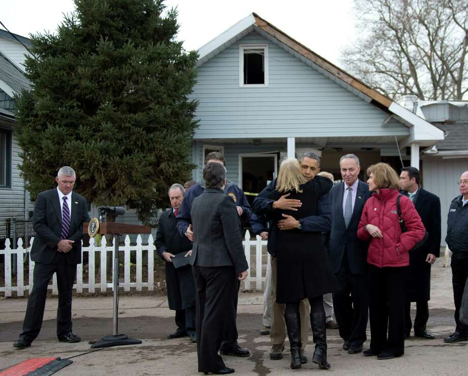 President Barack Obama, accompanied by New York City Mayor Michael Bloomberg, New York Gov. Andrew Cuomo, Homeland Security Secretary Janet Napolitano, Sen. Charles Schumer, D.N.Y., and other, hugs Sen. Kirsten Gillibrand, D-N.Y., after a news conference on Cedar Grove Avenue, a street significantly impacted by Superstorm Sandy, Thursday, Nov. 15, 2012, on Staten Island, in New York. Photo: Carolyn Kaster, AP / AP
