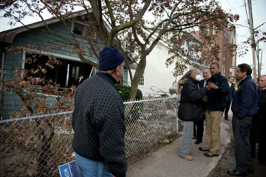 President Barack Obama, accompanied by Sen. Charles Schumer, D-N.Y., New York Gov. Andrew Cuomo, and New York City Mayor Michael Bloomberg, visits with resident Debbie Ingenito on Cedar Grove Avenue, a street significantly impacted by Superstorm Sandy, Thursday, Nov. 15,2012, on Staten Island, in New York. Photo: Carolyn Kaster, AP / AP