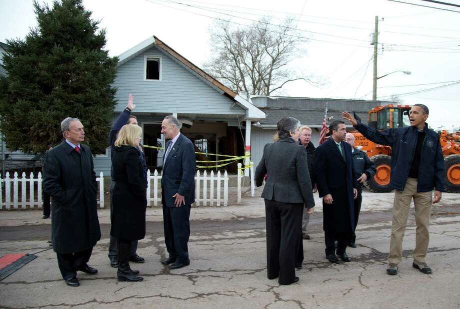 President Barack Obama waves to New York Gov. Andrew Cuomo, second from left, as he leaves a news conference on Cedar Grove Avenue, a street significantly impacted by Superstorm Sandy, Thursday, Nov. 15,2012,  on Staten Island,  in New York. From left are, New York City Mayor Michael Bloomberg, Cuomo, Sen. Kirsten Gillibrand, D-N.Y., Sen. Charles Schumer, D-N.Y., and Homeland Security Secretary Janet Napoitano. Photo: Carolyn Kaster, AP / AP