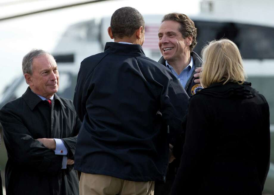 President Barack Obama, accompanied by Sen. Kirsten Gillibrand, D-N.Y., right, is greeted by New York Gov. Andrew Cuomo, second from right, and New York Mayor City Michael Bloomberg as he arrives at JFK International Airport in New York, Thursday, Nov. 15, 2012, en route to visit areas devastated by Superstorm Sandy. Photo: Carolyn Kaster, AP / AP