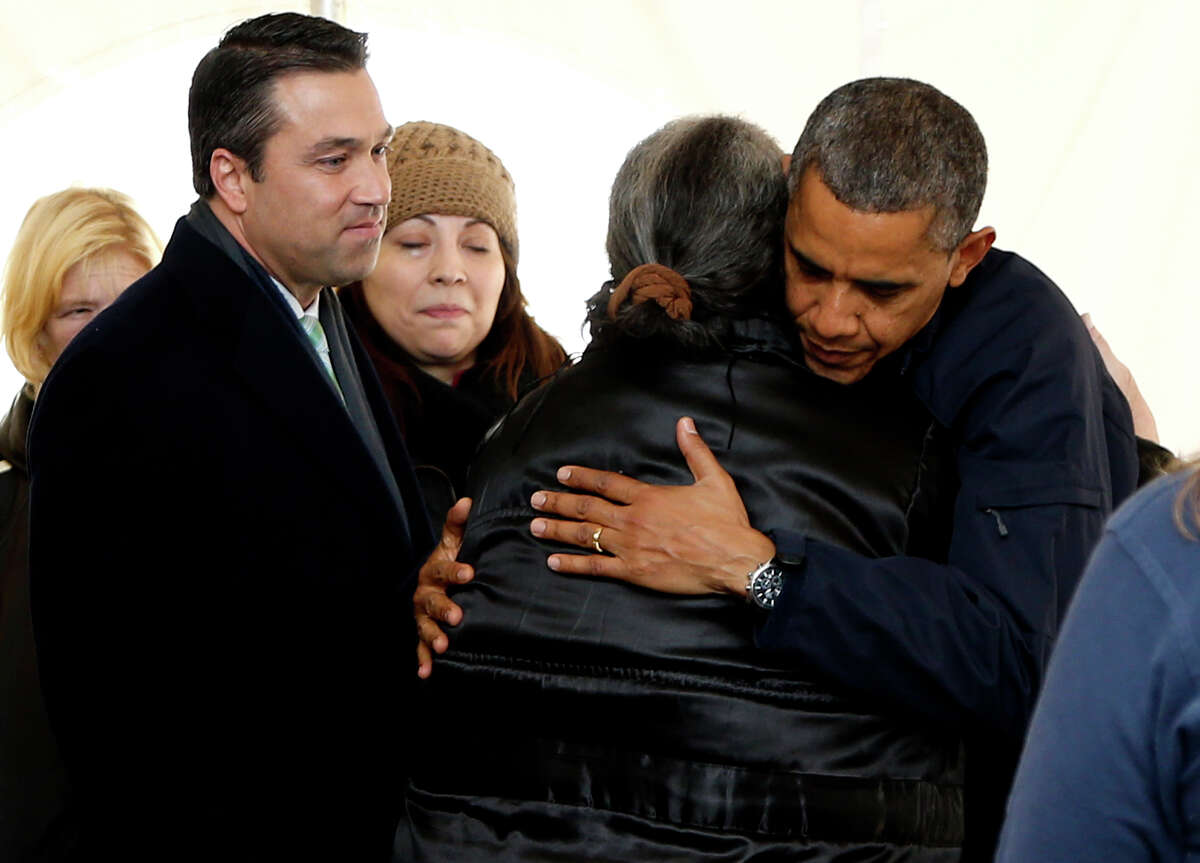 President Barack Obama hugs a woman as he visits the FEMA recovery center on the grounds of New Dorp High School, Thursday, Nov. 15, 2012 on Staten Island, in New York. At left is Rep. Michael Grimm, R-N.Y.
