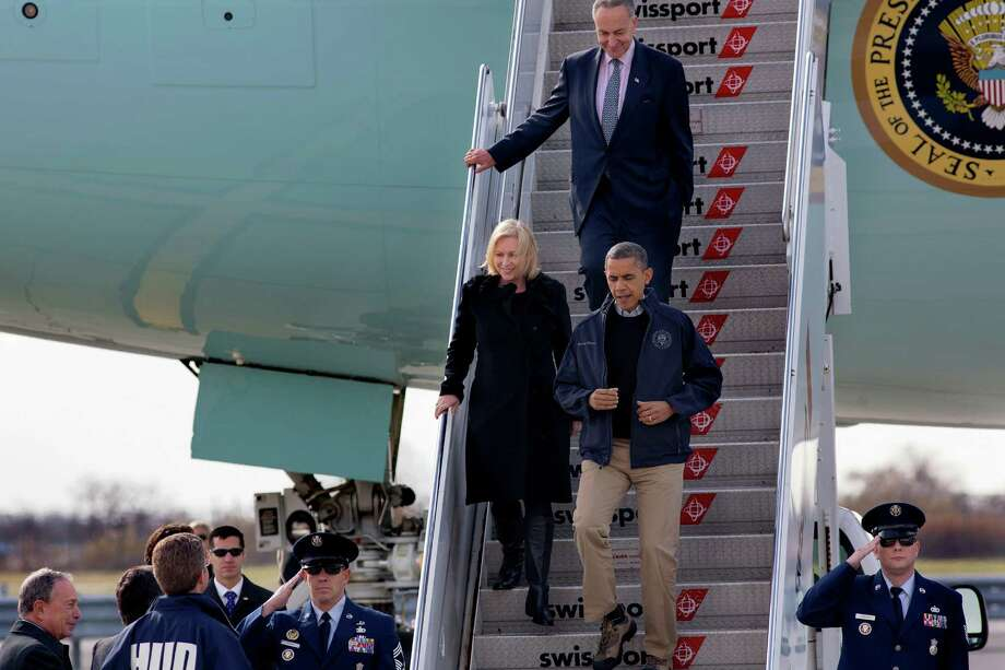 President Barack Obama, followed by Sen. Kirsten Gillibrand, D-N.Y,  and Sen. Charles Schumer, D-N.Y.,  arrive at JFK International Airport in New York, Thursday, Nov. 15, 2012, before being greeted by New York City Mayor Michael Bloomberg, left, Housing and Urban Development Secretary Shaun Donovan, in HUD jacket, and other state, local and federal officials, before taking an aerial tour of damage along the New York coastline in the wake of Superstorm Sandy. Photo: Craig Ruttle, AP / FR61802 AP