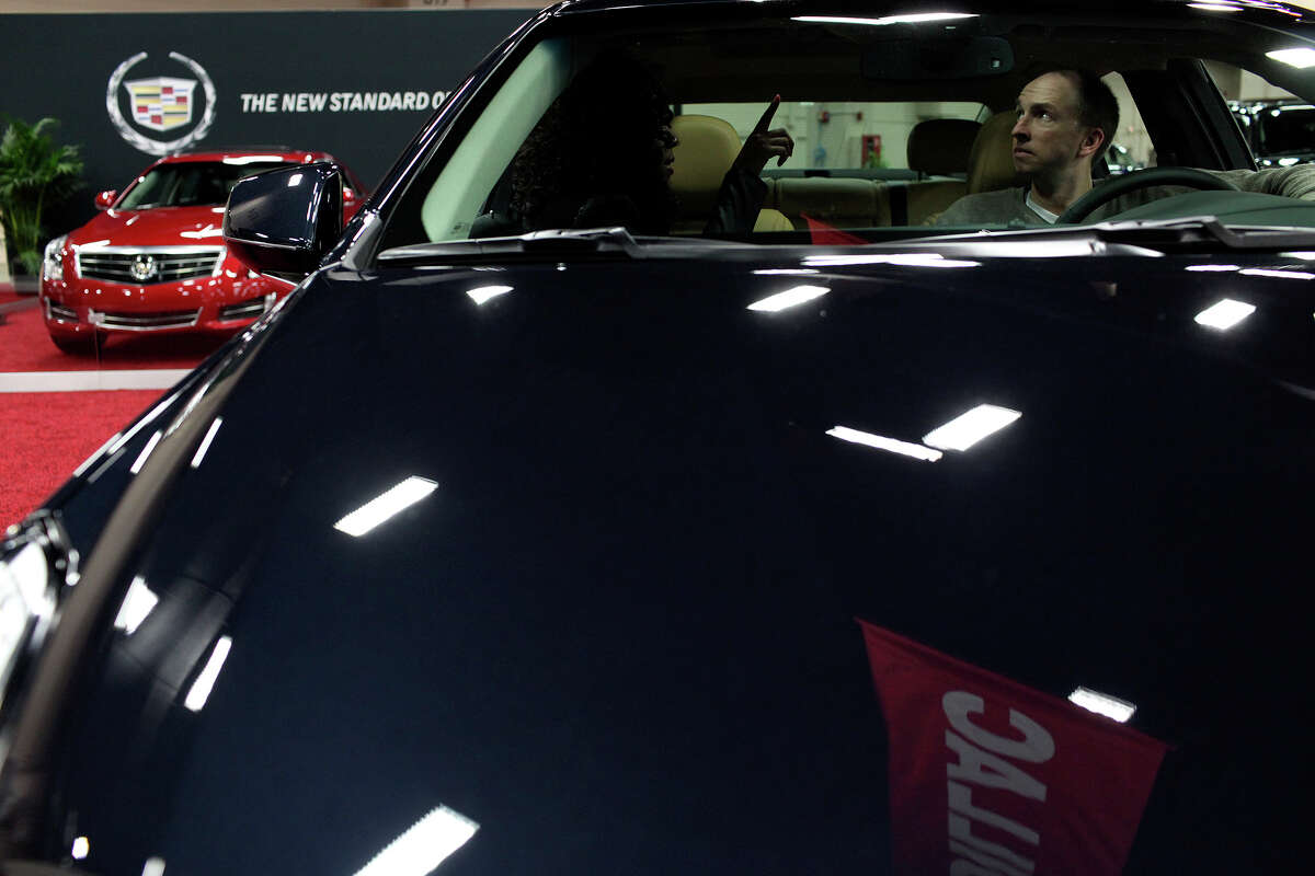 Joe Lyons, right, looks at a 2013 Cadillac XTS with the help of Cadillac product specialist Ashley Jackson during the San Antonio Auto and Truck Show at the Henry B. Gonzalez Convention Center on Thursday, Nov. 15, 2012.