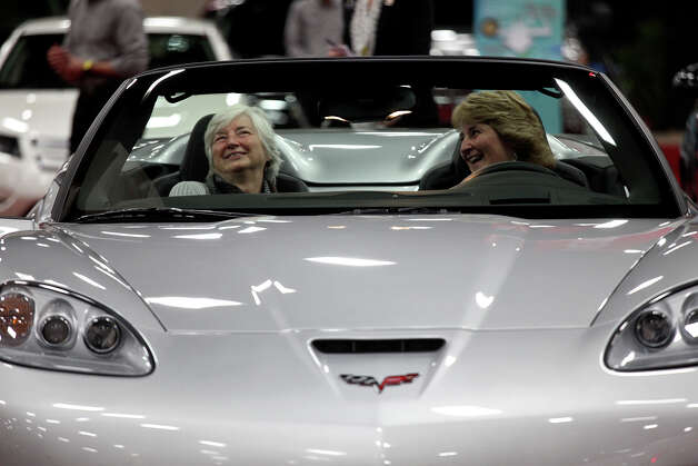 Gloria Whitsel, of Grand Prarie, left, and Melanie Kaiser, of Maine, right, try out a 2013 Chevy Corvette Grand Sport Convertible during the San Antonio Auto and Truck Show at the Henry B. Gonzalez Convention Center on Thursday, Nov. 15, 2012. Kaiser's husband is being honored at the show as a Master Technician of the Year with General Motors. Photo: Lisa Krantz, San Antonio Express-News / © 2012 San Antonio Express-News