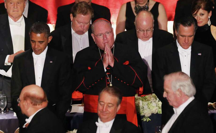 Roman Catholic Cardinal Timothy Dolan prays in October with presidential candidates at his side. Catholics lack a natural political home in today's partisan environment. Photo: Mario Tama, Getty Images / 2012 Getty Images