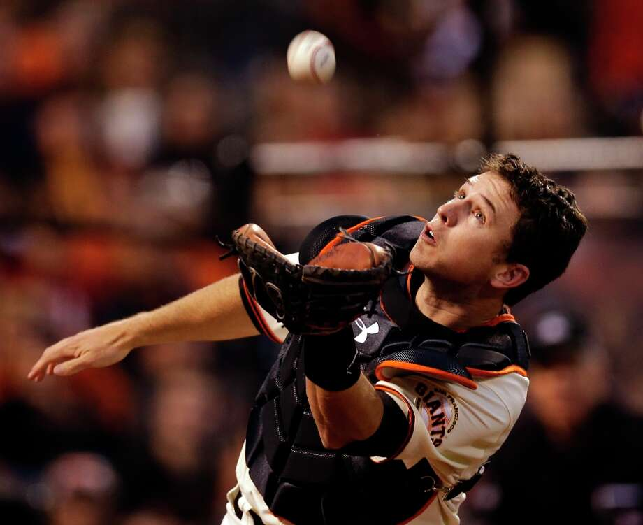 San Francisco Giants catcher Buster Posey makes a diving catch on a foul ball hit by St. Louis Cardinals' Matt Holliday during the fourth inning of Game 1 of baseball's National League championship series Sunday, Oct. 14, 2012, in San Francisco. Photo: David J. Phillip, Associated Press / AP