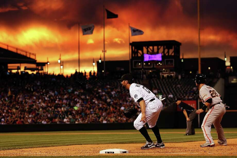 First baseman Todd Helton #17 of the Colorado Rockies plays defense and Buster Posey #28 of the San Francisco Giants leads off first base as sunset falls over the stadium at Coors Field on August 3, 2012 in Denver, Colorado. Photo: Doug Pensinger, Getty Images / 2012 Getty Images