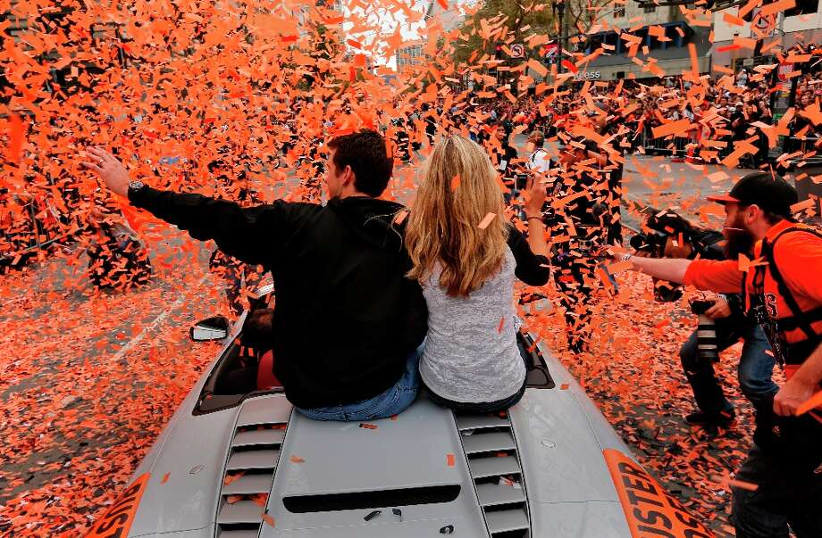 Giants' catcher Buster Posey and his wife Kristen pass through a stream of confetti as the San Francisco Giants celebrated their World series Championship with a parade up Market Street in downtown San Francisco, Calif., on Wednesday Oct. 31, 2012. Photo: Michael Macor, The Chronicle / ONLINE_YES