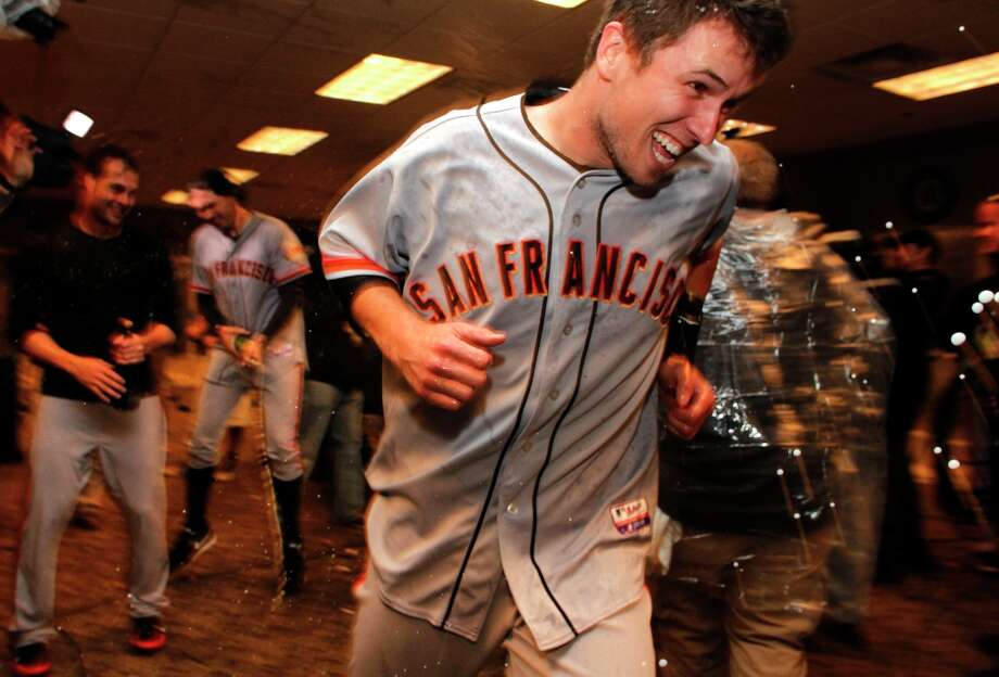 Giants' Buster Posey escapes a spray of champagne as the team celebrates in the clubhouse, as the San Francisco Giants beat the Cincinnati Reds 6-4 in game five to win the National League Division Series in Cincinnati, Ohio on Thursday Oct. 11, 2012. Photo: Michael Macor, The Chronicle / ONLINE_YES
