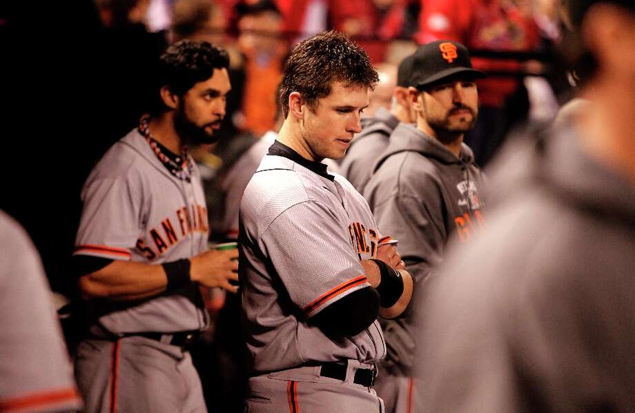 Giants' Buster Posey and teammates Angel Pagan (left) and Xavier Nady, (right)  watch from the dugout in the ninth inning, as the San Francisco Giants went on to lose to the St. Louis Cardinals 8-3 in game four of the National League Championship Series, on Thursday Oct. 18, 2012 at Busch Stadium , in  St. Louis, Mo. St. Louis now leads the series three games to 1. Photo: Michael Macor, The Chronicle / ONLINE_YES