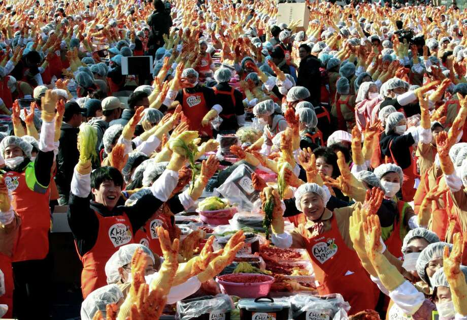 Volunteers hold up kimchi, a traditional Korean pungent vegetable, as they make it to donate to needy neighbors in preparation for the winter season, in front of the Seoul City Hall in Seoul. South Korea, Thursday, Nov. 15, 2012. About 2,200 housewives made 270 tons of kimchi. Made with cabbage, other vegetables and chili sauce, kimchi is the most popular traditional food in Korea. Photo: Ahn Young-joon, AP / Yonhap