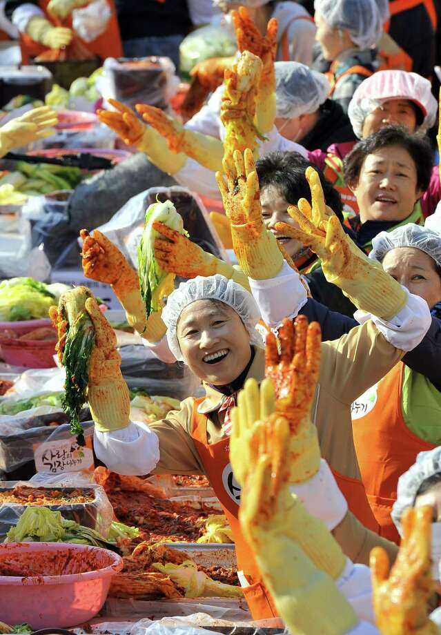 South Korean volunteers pose for a photo as they make 140 tons of kimchi, a traditional Korean dish of spicy fermented cabbage and radish, in a park outside the metropolitan government building in Seoul on November 15, 2012. City officials will hand out kimchi to about 14,000 poor households in an event marking the start of the winter season. AFP PHOTO / JUNG YEON-JEJUNG YEON-JE/AFP/Getty Images Photo: JUNG YEON-JE, AFP/Getty Images / AFP