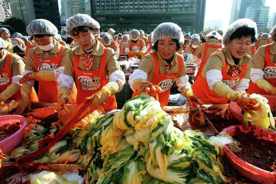 Volunteers make kimchi, a traditional South Korean pungent vegetable, to donate to needy neighbors in preparation for the winter season, in front of the Seoul City Hall in Seoul, South Korea, Thursday, Nov. 15, 2012. About 2,200 housewives made 270 tons of kimchi. Made with cabbage, other vegetables and chili sauce, kimchi is the most popular traditional food in Korea. Photo: Ahn Young-joon, AP / AP