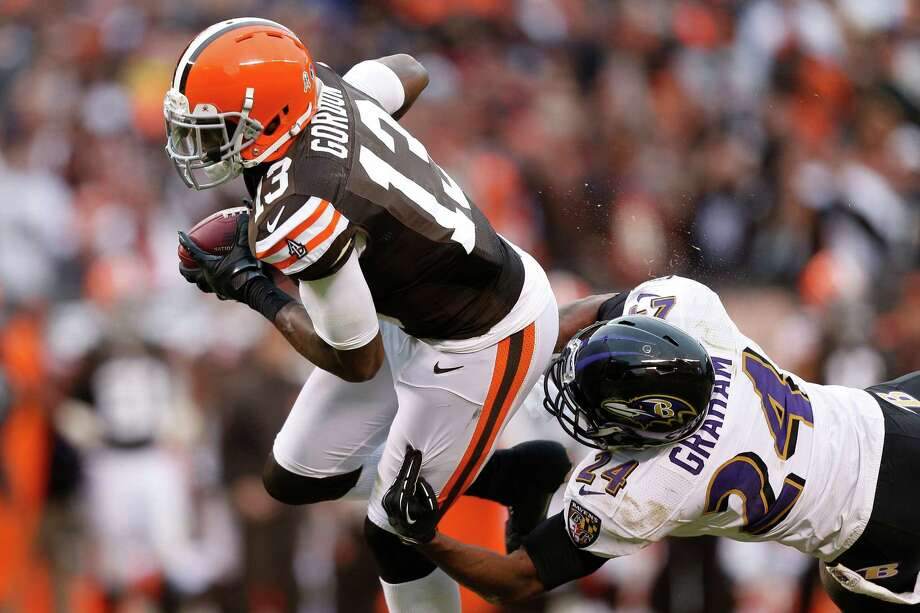 Cleveland Browns wide receiver Josh Gordon (13) breaks a tackle by Baltimore Ravens defensive back Corey Graham (24) in Cleveland, Sunday, Nov. 4, 2012. (AP Photo/Rick Osentoski) Photo: Rick Osentoski, Associated Press / FR170444 AP