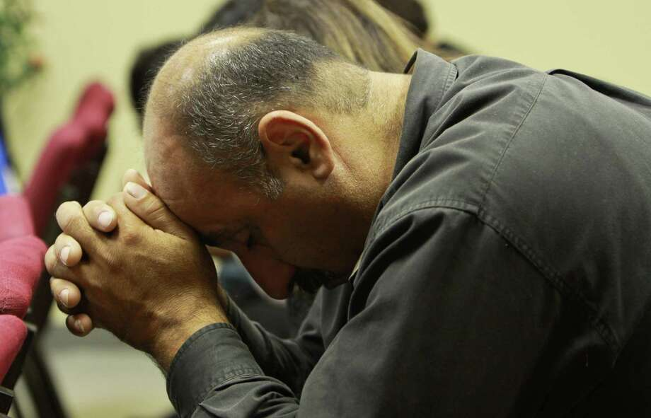 Nabil Shehada, above, prays during the service at the Arabic Christian Church. Below, Lana and Sal Nimri, from left, and Hassan Awadalla worship at the Arabic Christian Church. Photo: Gary Fountain, Freelance / Copyright 2012 Gary Fountain.