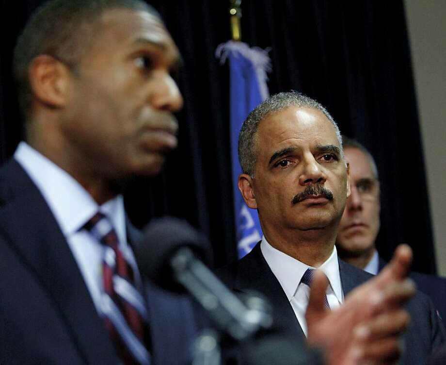 U.S. Attorney General Eric Holder (right) looks on in a New Orleans courtroom as his associate Tony West explains the settlement with BP over the 2010 Deepwater Horizon oil spill. Photo: Matthew Hinton, Associated Press